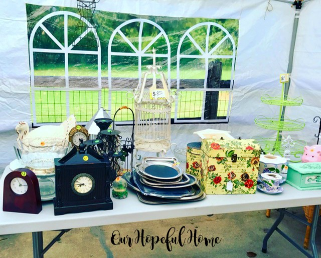 garage sale table filled with clocks trays dishware birdcage