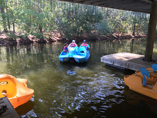 Sheryl, her husband and grandson pulling away from dock in a paddle boat