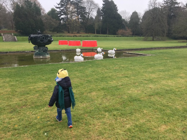 Sun-and-ice-toddler-in-park-with-red-drums-and-swans