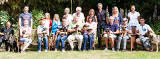 A group photo of the new walkers with their puppies sat in the garden