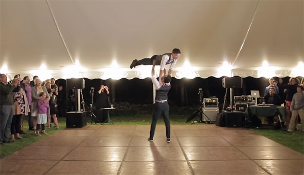 screenshot from the video of the lift, with one man holding the other high over his head in the middle of the dance floor
