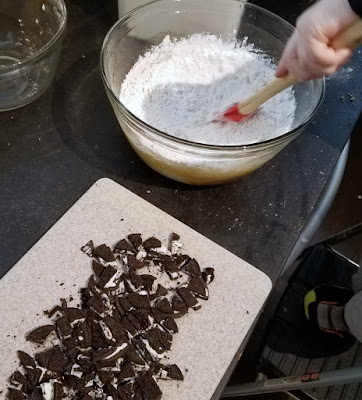 stirring together blondie batter with spatula, cutting board of chopped oreos nearby