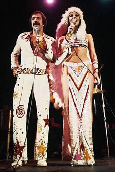 Sonny and Cher in concert. Costumed in bedazzled jumpsuit and Indian headdress / loincloth.