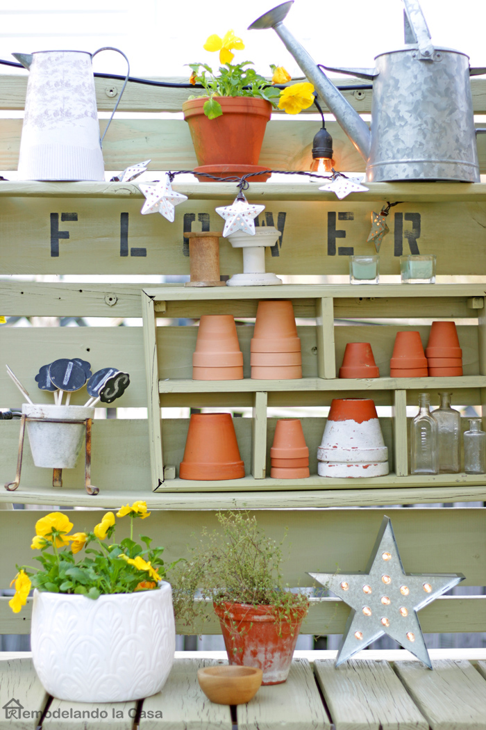 green potting bench with flower market sign and lots of terra cotta pots and watering cans on it.