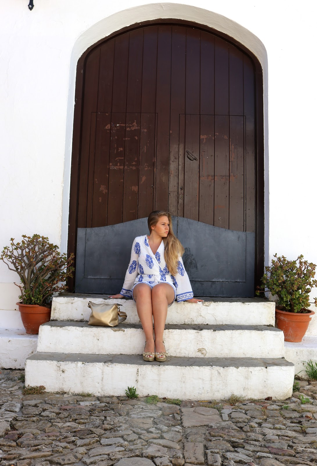 Blonde girl, Katie Heath wearing blue and white playsuit from Quiz in Castillo de Castellar, Spain