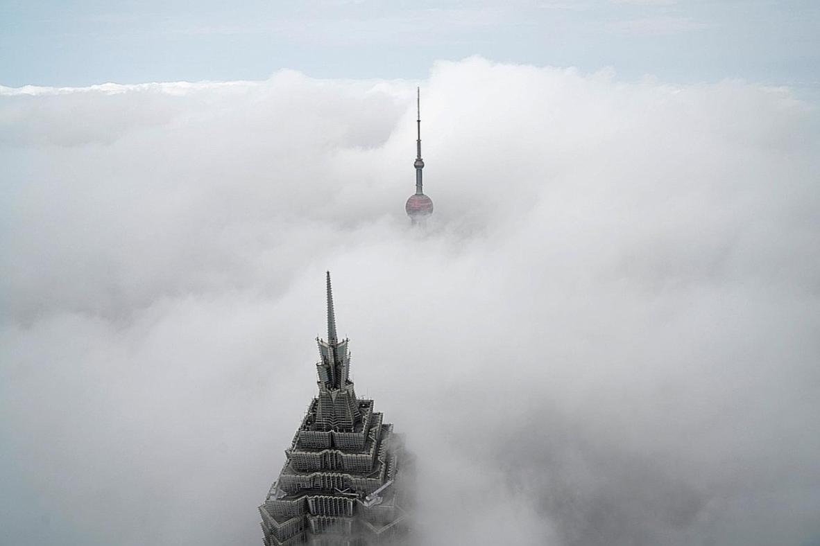 A dense fog engulfed Shanghai on Tuesday morning, affecting road, water and air traffic while transforming the city into a