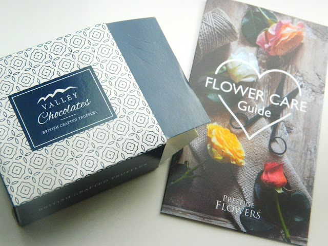 A photo showing a box of chocolate truffles and a flower bouquet care guide