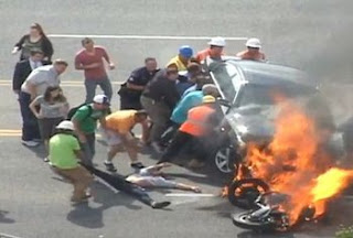 bystanders working together to rescue someone from a burning car