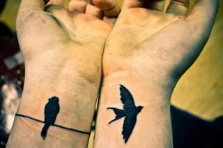 Dos chicas juntan sus muñecas para enseñarnos sus tatuajes de dos pajaros uno volando y el otro en un cable posado