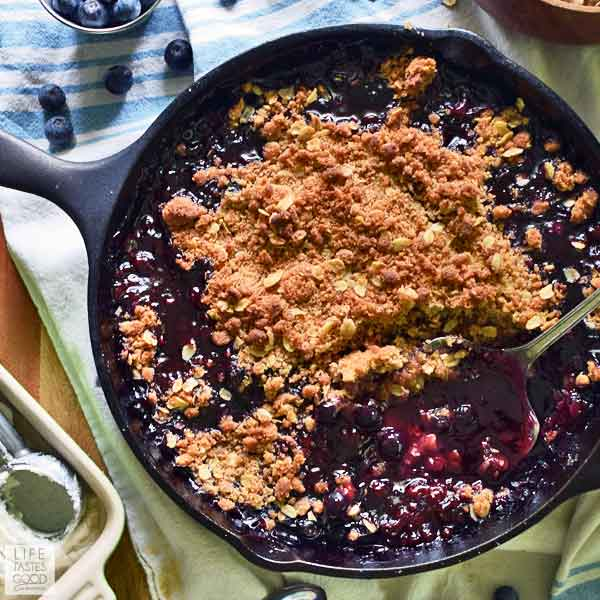Overhead view of blueberry crisp recipe in a cast iron skillet with a spoon