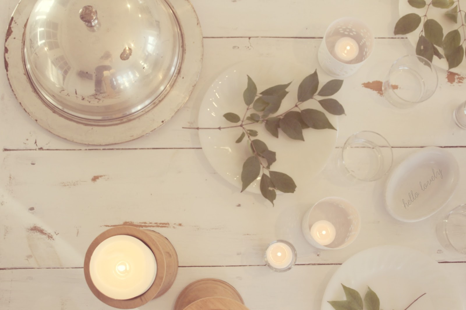 White farmhouse table with silver food dome, candlelight, and greenery by Hello Lovely Studio
