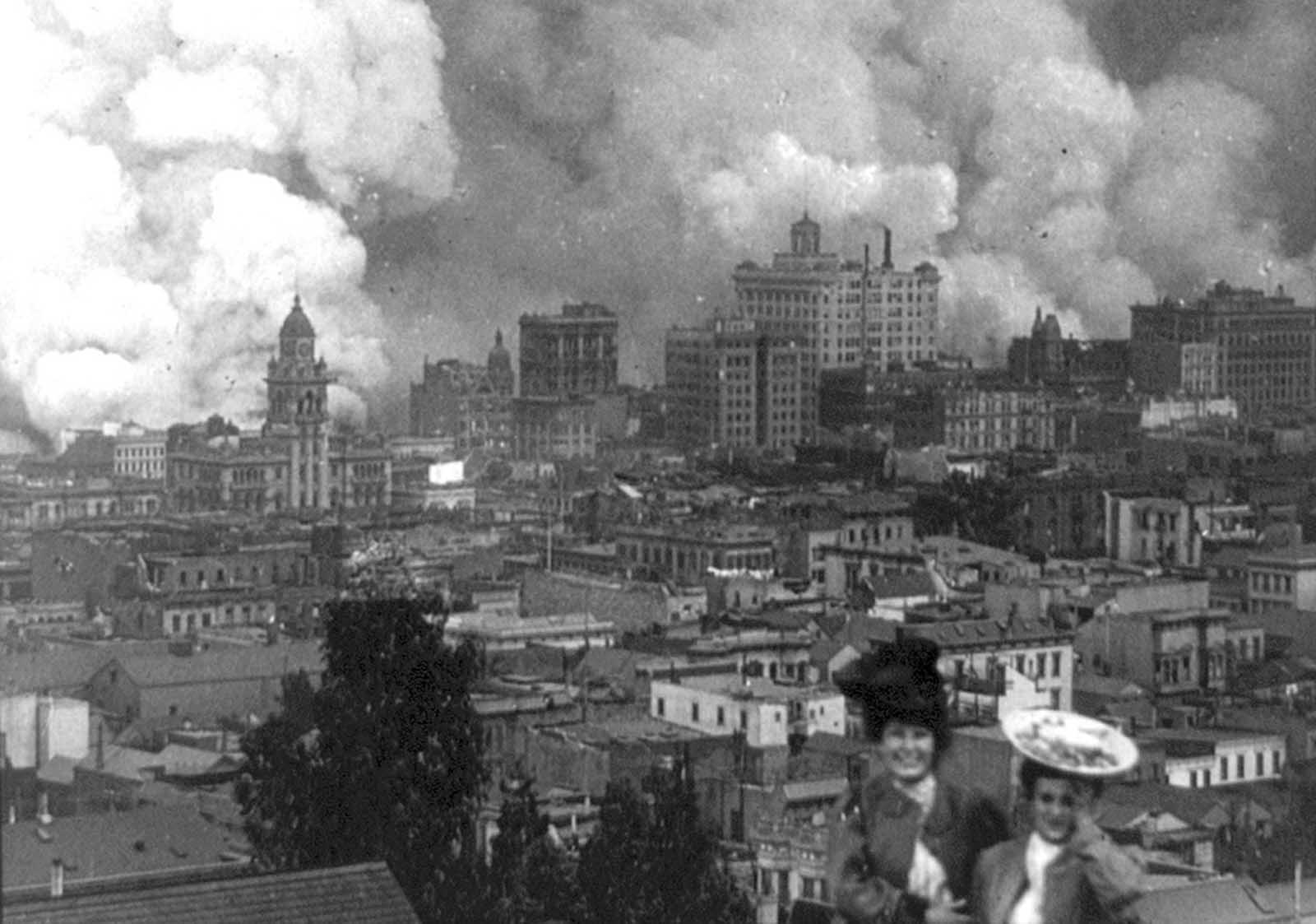 Onlookers pose for a photograph as San Francisco burns in the background on April 18, 1906.