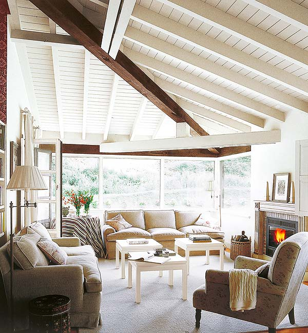 Living room with beamed ceiling, fireplace, taupe sofas and armchairs, wood floor, picture window and three small white coffee tables
