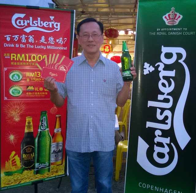 See Seng Hong, a potential 'Carlsberg Millionaire' poses with a large bottle of Carlsberg and custom 'ang pows' from the brewer..