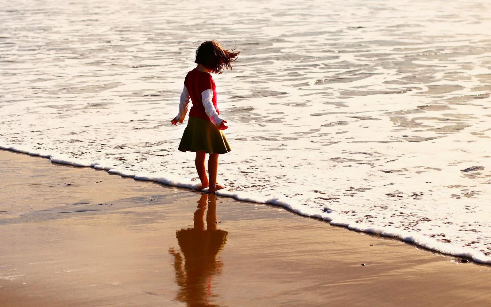 Meisje op strand in water van zee