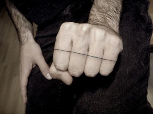 Uma fina linha preta é executado ao longo de todos os quatro dedos sobre o portador da mão esquerda essa tatuagem.