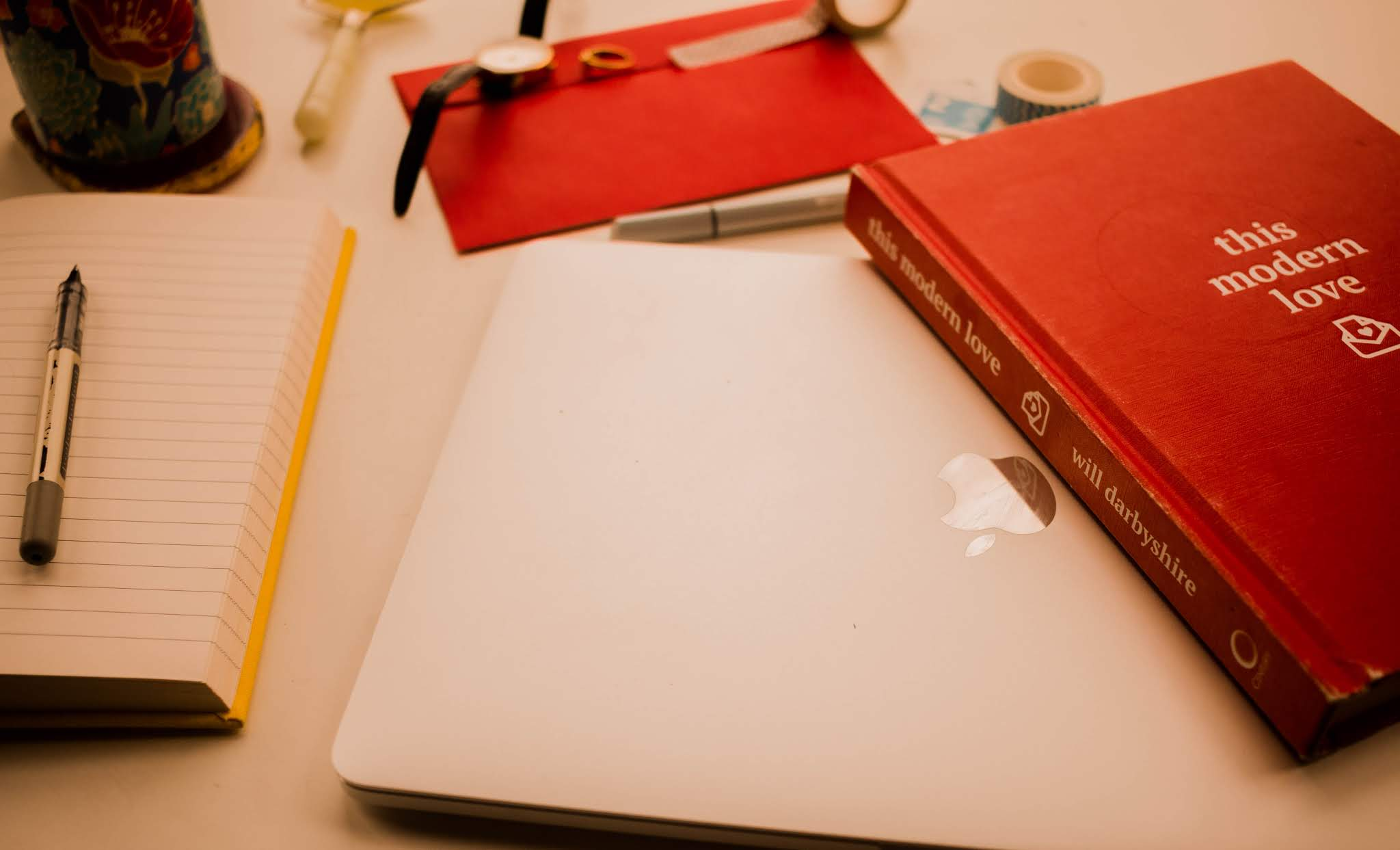 Flatlay image: macbook pro, book this modern love, notebook, pen - Newsletter recommdendations blog post