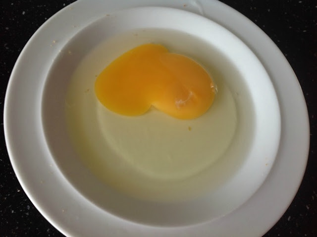 Whole egg broken on white plate