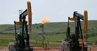 Pumpjacks and methane flare (Credit: AP Photo/Charles Rex Arbogast, File) Click to Enlarge.