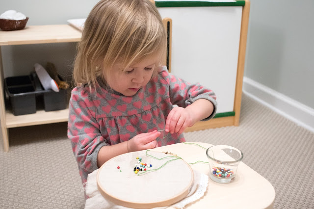 Montessori at home activity - bead sewing for a 3-year-old.