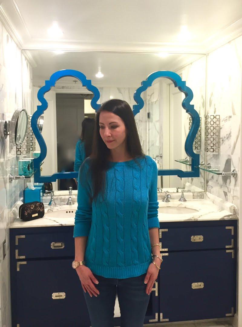 Wearing a blue sweater and jeans that match the blue decor of the hotel bathroom.