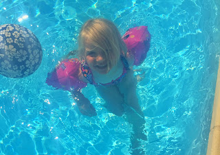 3 year old girl with arm bands in a bright blue swimming pool