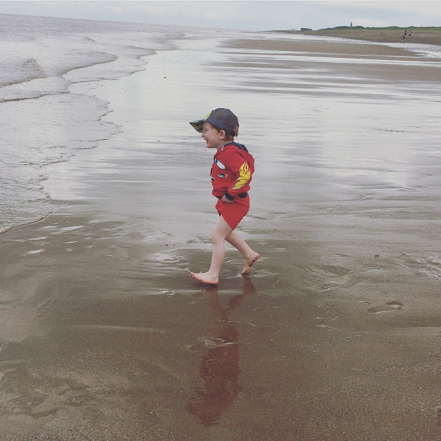 Little boy running into the sea for a paddle
