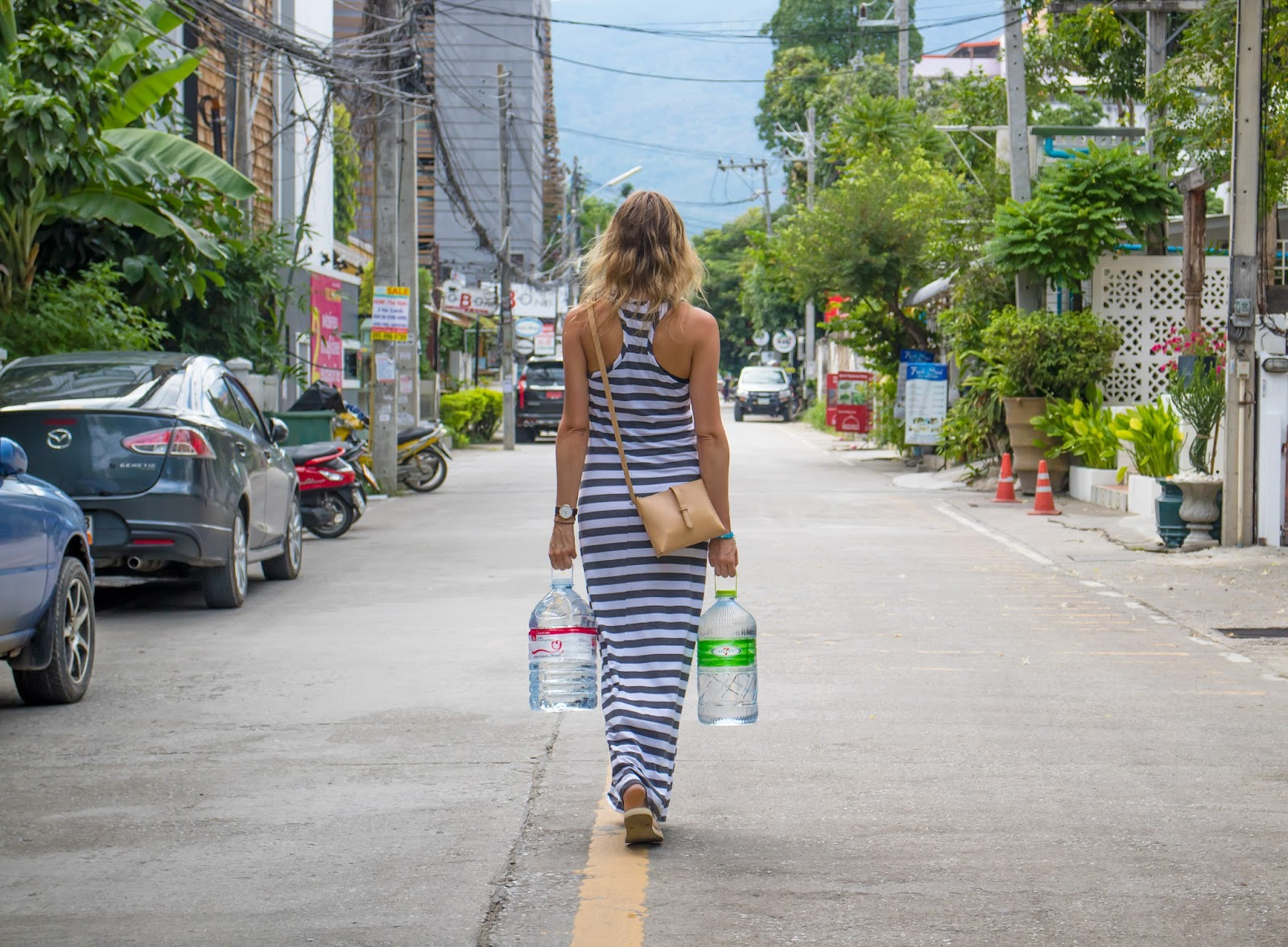 Travel Blogger and digital nomad, Alison Hutchinson, is carrying water refills on the streets of Nimman, Chinag Mai