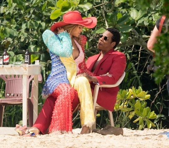 Power couple! Beyonce flaunts major cleavage in jumpsuit as she sits on Jay-Z's lap for colourful photo shoot in Jamaica (Photos)