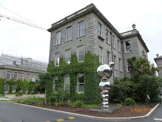 Kunstwerk met gestapelde bollen en gebouw Trinity College