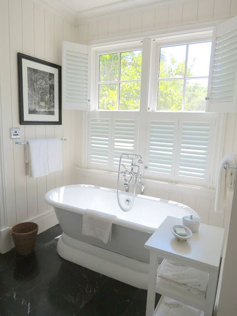 Beautiful bathroom with white plantation shutters and freestanding tub