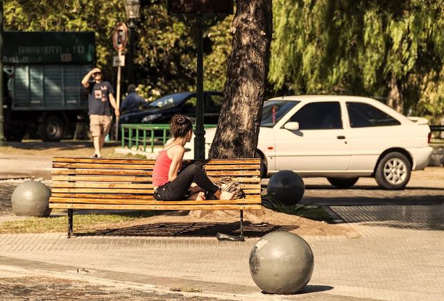 Joven en banco de plaza al sol