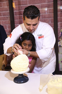 A young member of the audience gets up-close and personal with Buddy and learns a thing or two about decorating a cake.
