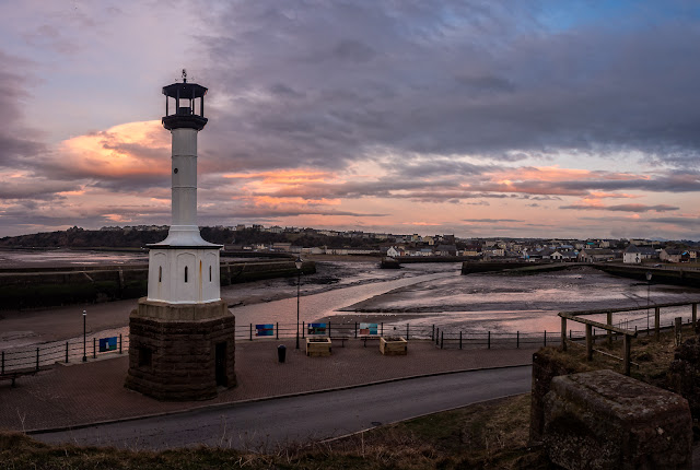 Photo of Maryport lighthouse at sunset with the town in the distance