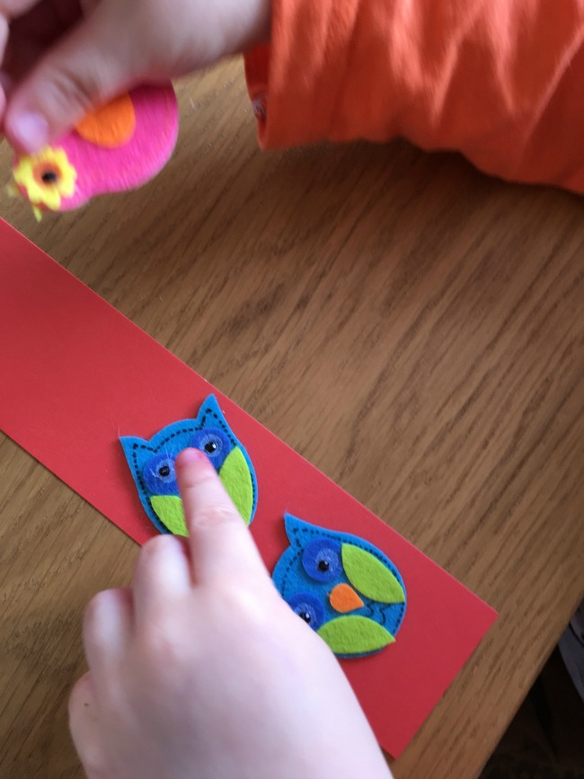 toddler placing owl stickers on bookmark
