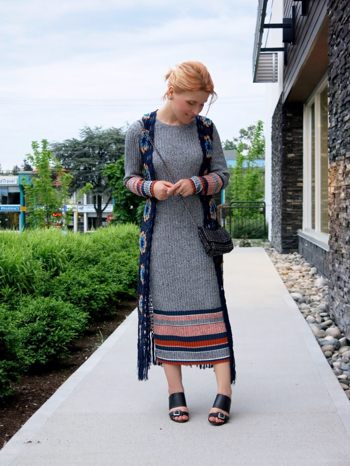 styling a sweater dress with a long crochet vest, wedge slides, and cross body bag