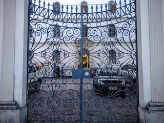 Fotografia colorida. Portão de entrada do edifício antigo, em ferro decorado, e, ao fundo, parte da fachada.