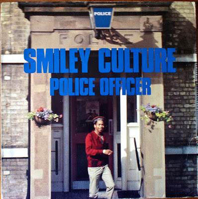 Smiley Culture's 'Police Officer' 12inch 45rpm single, Fashion Records, cover, outside Brixton(?) police station, 1984