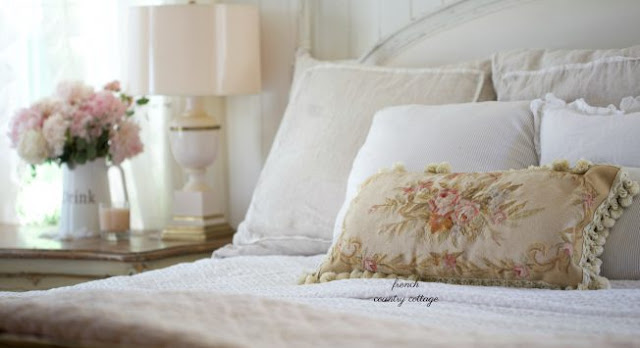 floral needlepoint pillow on bed
