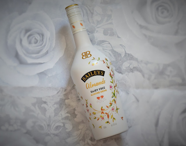 A bottle of Baileys Almande on a floral grey/white background.