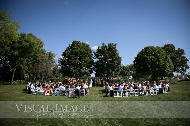 Wedding guests seated in white chairs near formal gardens in Frame Park
