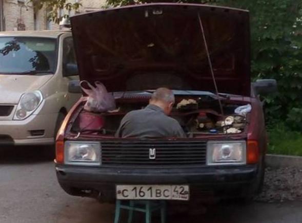 Seseorang yang sedang mengservice mesin mobil