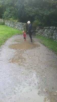 Mummy and toddler jumping in puddles