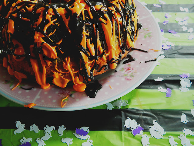 Orange and black frosting drizzled over a bundt cake