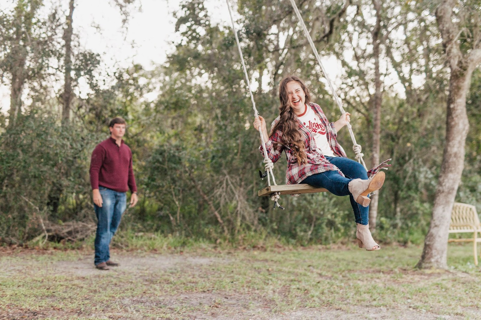 Brunette boy pushing brunette girl on a swing in the North Florida woods
