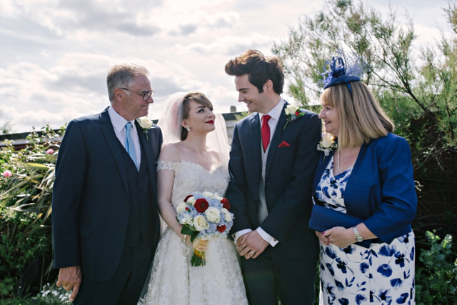 Bride and groom with mother and father of groom at vintage seaside wedding