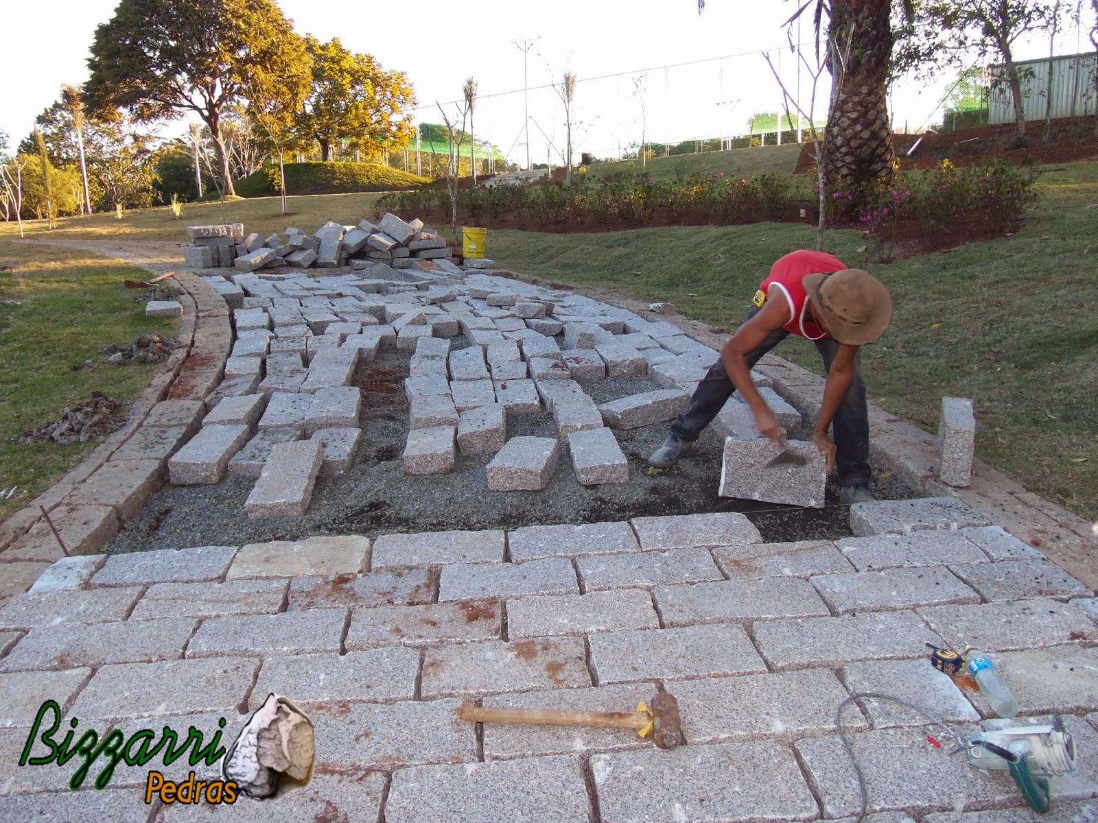 Execução do calçamento de pedra com as guias de pedra na entrada da residência em sítio em Piracaia-SP.