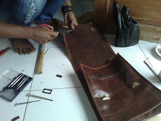 memasang aksesoris tas kulit