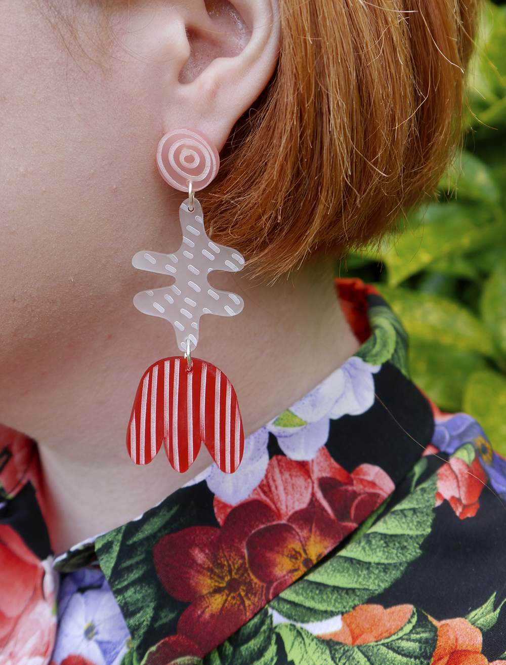 Red, pink and white acylic earrings with etched patterns by Julia de Klerk