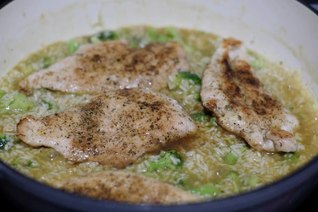 The fully cooked chicken being placed on top of the broccoli, chicken, and rice mixture.
